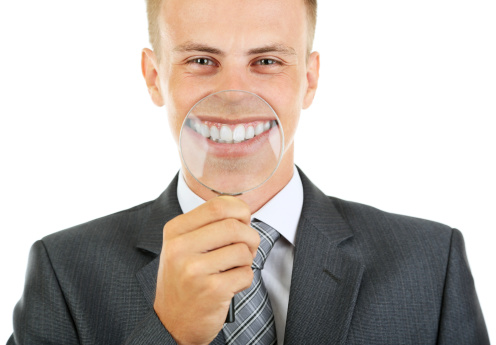 Man in suit with magnifying glass in front of his smile after getting Zoom Teeth Whitening at La Jolla Dental in La Jolla, CA