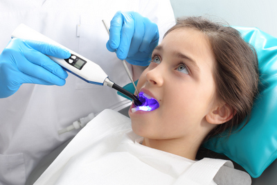 La Jolla Dentist providing a patient with Dental Sealants to help you keep their smile at La Jolla Dental in La Jolla, CA